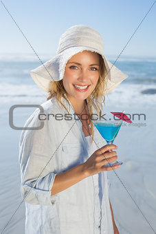 Smiling blonde relaxing by the sea holding cocktail