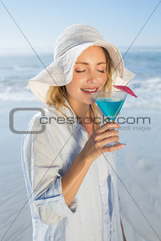 Smiling blonde relaxing by the sea sipping cocktail
