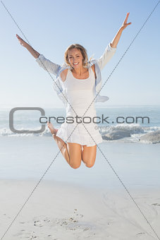 Smiling blonde leaping by the sea