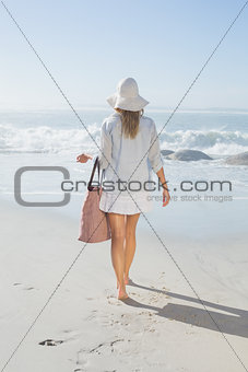 Blonde woman in sunhat carrying beach bag looking out to sea