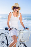 Gorgeous happy blonde on a bike ride at the beach