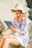 Gorgeous happy blonde using tablet pc at the beach