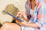 Woman using tablet pc at the beach