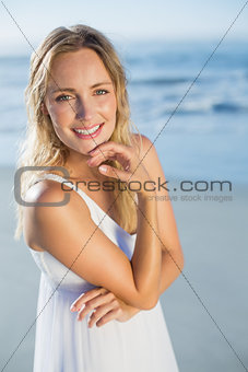 Pretty blonde standing at the beach in white sundress smiling at camera