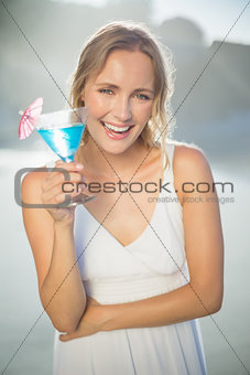 Smiling blonde standing at the beach in white sundress with blue cocktail