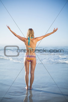 Blonde standing on the beach in bikini with arms out