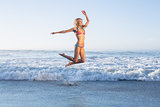 Happy blonde leaping on the beach in bikini