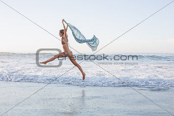 Happy blonde leaping on the beach in bikini with a scarf