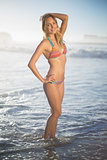 Happy blonde standing in the sea posing in bikini