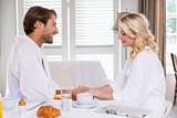 Cute couple having breakfast in their bathrobes
