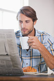 Handsome man drinking coffee and reading newspaper