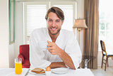 Handsome man having breakfast in his bathrobe smiling at camera