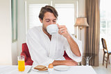 Handsome man having breakfast in his bathrobe drinking coffee