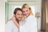 Cute couple in bathrobes smiling at camera