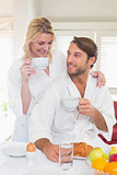 Cute couple in bathrobes having breakfast together