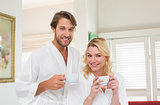 Cute couple in bathrobes smiling at camera together holding cups