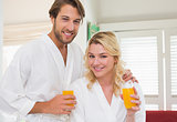 Cute couple in bathrobes smiling at camera together having breakfast