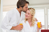 Cute couple in bathrobes drinking orange juice
