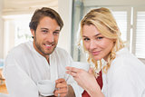 Cute couple in bathrobes having coffee together smiling at camera