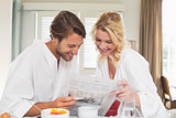 Cute couple in bathrobes having breakfast together reading the newspaper