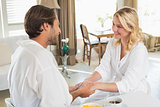 Cute couple in bathrobes having breakfast together holding hands