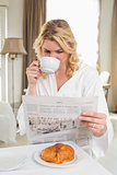 Pretty blonde in bathrobe drinking coffee and reading newspaper