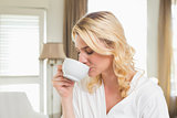 Pretty blonde in bathrobe drinking coffee