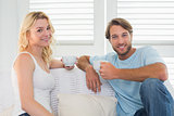 Smiling casual couple sitting on couch having coffee