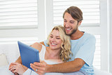 Smiling casual couple sitting on couch under blanket using tablet pc