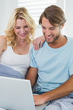 Cute casual couple sitting on couch using laptop