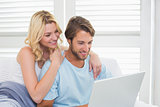 Happy casual couple sitting on couch using laptop