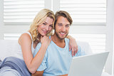 Happy casual couple sitting on couch using laptop smiling at camera
