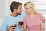 Happy couple drinking red wine together on the couch