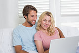Happy couple relaxing together on the couch using laptop