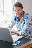 Smiling casual man using laptop looking at camera
