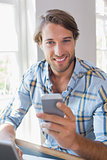 Smiling casual man using laptop and texting on smartphone
