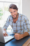 Smiling casual man using laptop to shop online