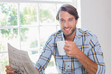Casual smiling man having coffee while reading newspaper