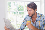Casual smiling man having orange juice while reading newspaper