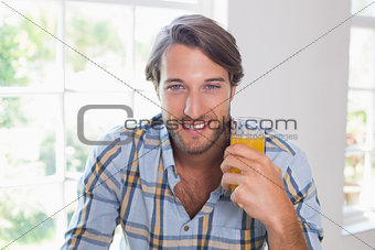 Casual smiling man having orange juice