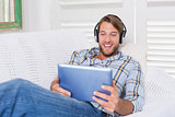 Casual smiling man lying on couch listening to music on tablet pc