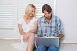 Cute young couple sitting on floor using laptop
