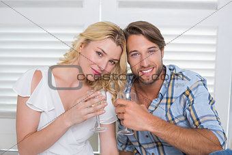 Cute young couple sitting on floor together having white wine
