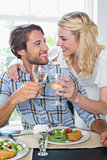 Cute smiling couple enjoying white wine over a meal together