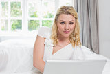 Pretty blonde lying on bed using laptop smiling at camera