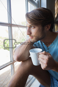 Thoughtful man sitting by the window having coffee