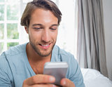 Handsome man sitting on bed sending a text message