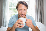 Handsome man sitting on bed drinking coffee