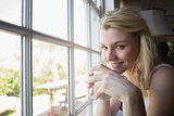 Pretty blonde sitting by the window having coffee