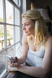 Pretty blonde sitting by the window sending a text